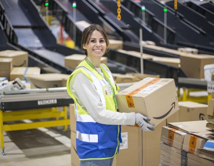 Piano americano di Ilaria di Bartolomeo, Operations Manager di Amazon a Casirate (Bergamo), mentre lavora nel centro di smistamento. Sorregge in mano un pacco con il sorriso di Amazon.