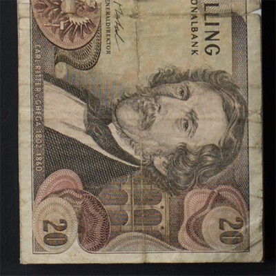 """Detail of a piece of old Austrian paper currency. The image includes the number 20 at the corners of the bank note as well as a well as a portrait of a man with a mustache. A label beneath the portrait says """"Carl Ritter v. Ghegha 1802 - 1860."""""""