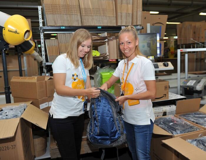 """Zwei MItarbeiterinnen von Amazon, beide tragen ein weißes Poloshirt mit orangenen Herzaufdruck und der Beschriftung """"Amazon Volunteer"""" stehen an einer Packstation, umgeben von Kartons. Sie halten in der Hand einen blauen Rucksack, den sie gerade beide mit verschiedenen Untensilien befüllen."""