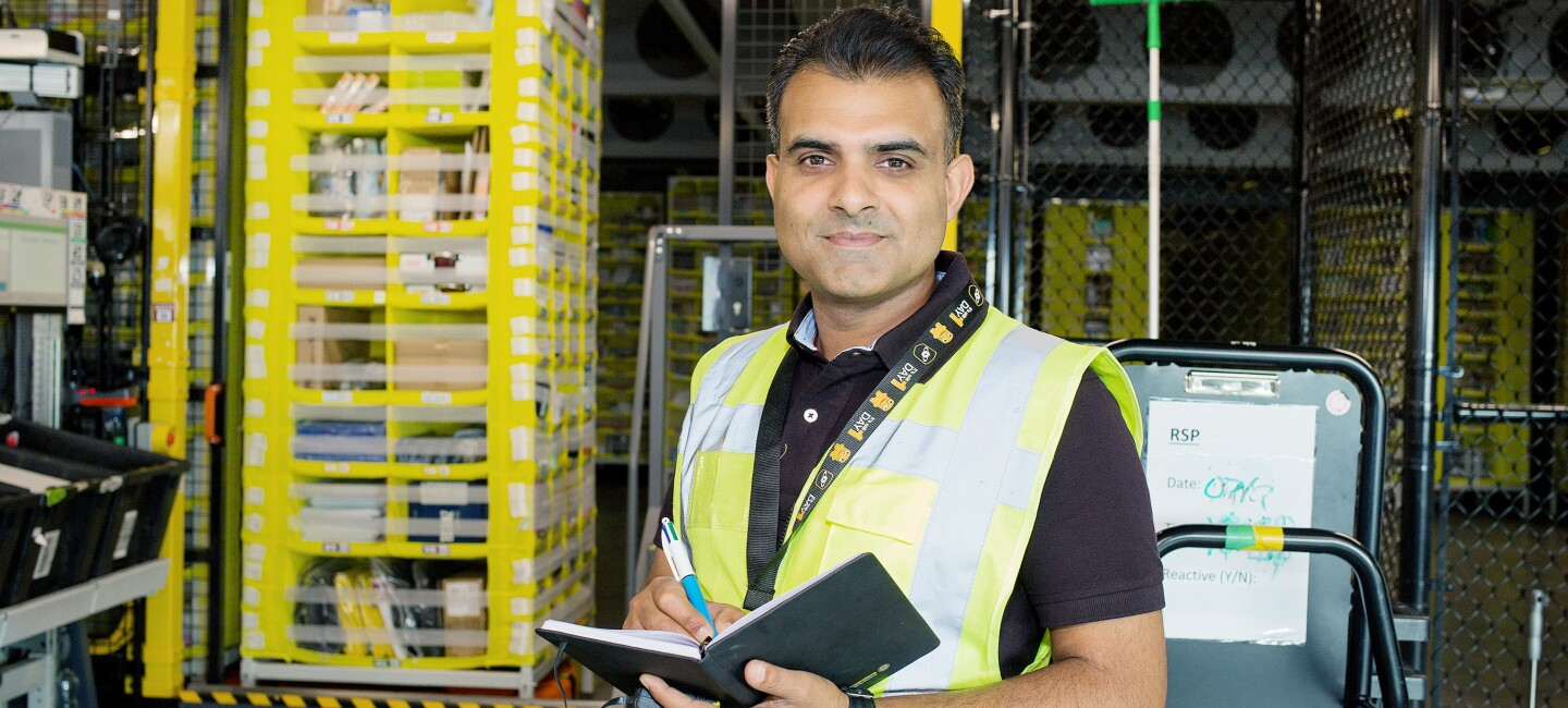 Amazon's ergonomics expert Raz Osman holding a notepad and looking directly at the camera