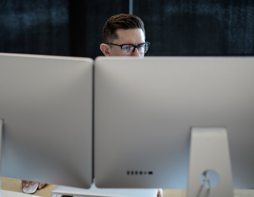 A man in glasses sits behind two large computer monitors.