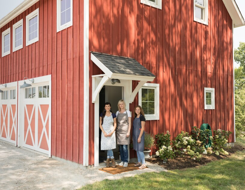 Three woman stand at the entrance of a tidy, red barn that has been converted into a workshop. All three women are wearing aprons.
