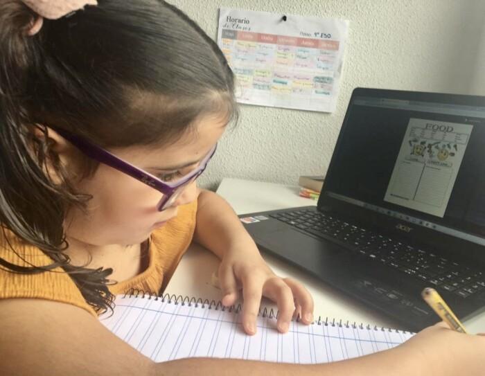 Hay una niña de 4 de ESO con gafas moradas, pelo rizado por el hombro y con un lápiz en la mano y una libreta. Está en su escritorio con un ordenador que hay una página de deberes con la palabra inglesa food. De fondo una pared blanco y un horario escolar colgado.