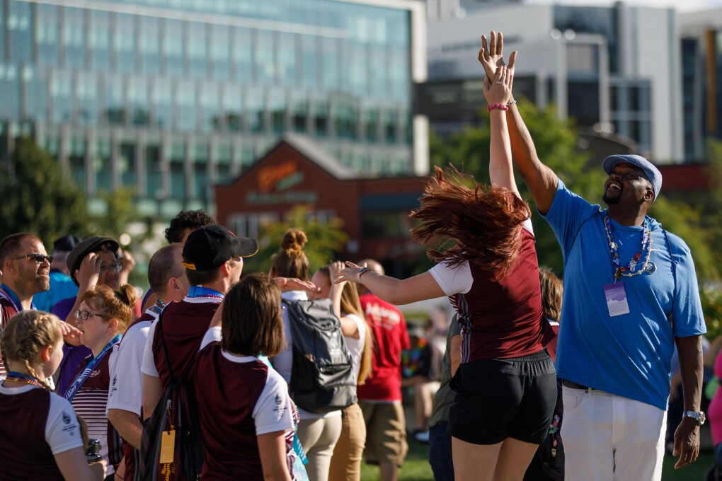 A high five is given at the Special Olympics closing ceremony. To make the high-five happen, a woman is jumping up to reach the hand of a male volunteer's hand.