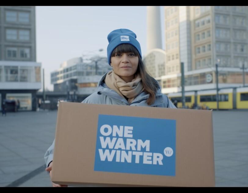 """Eine dunkelhaarige Frau mit blauer Mütze schaut in die Kamera. Sie steht auf einem Platz und hat eine Winterjacke an. In der Hand hält sie einen Karton auf dem """"One Warm Winter"""" steht."""