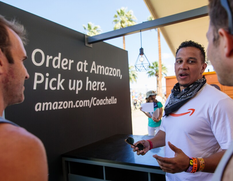 "Three men talk with each other. The man in the center wears a T-shirt with the Amazon smile logo. A sign in the background reads ""Order at Amazon, Pick up here. amazon.com/Coachella"""