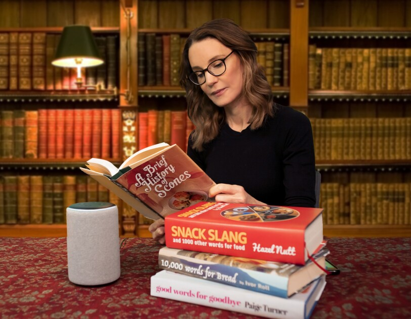 Susie Dent wearing glasses sat at a table, reading books about language and dialect