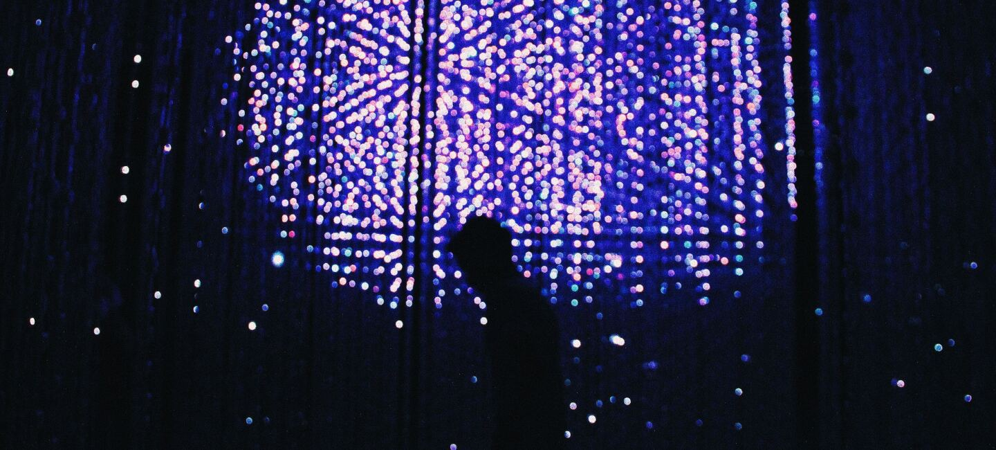 Image of a man walking in front of a wall of lights at night