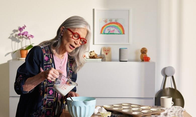 Lady with long grey hair and red glasses, using Echo Plus for baking