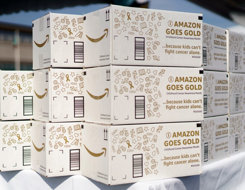 "Stacks of white Amazon Goes Gold boxes on a table. The boxes are illustrated with icons ranging from kites, bicycles, slides, hearts, and others, and wording that says ""Amazon Goes Gold, Childhood Cancer Awareness Month ...because kids can't fight cancer alone. #GoGold"""