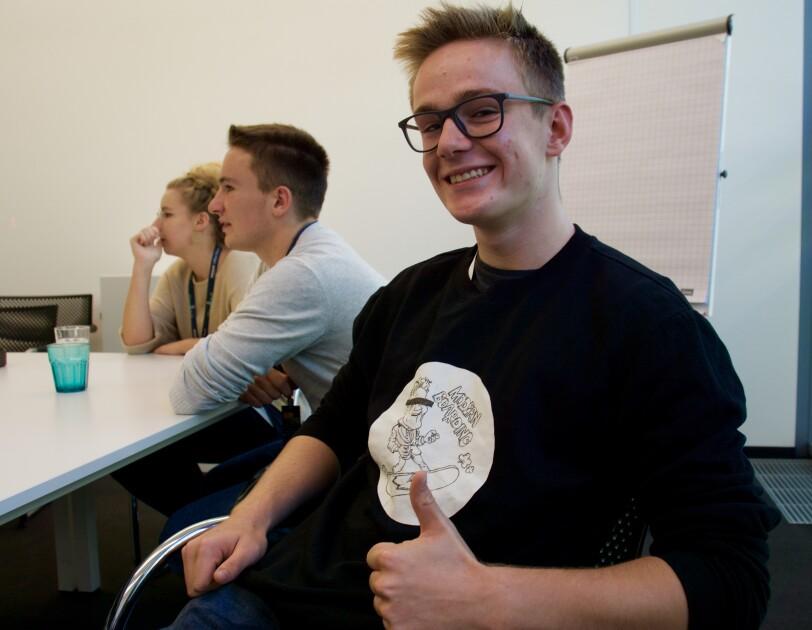 Ein etwa 17-jähriger Schüler sitzt auf einem Stuhl in einem Konferenzraum. Er trägt ein schwarzes Shirt und hält den Daumen nach oben.