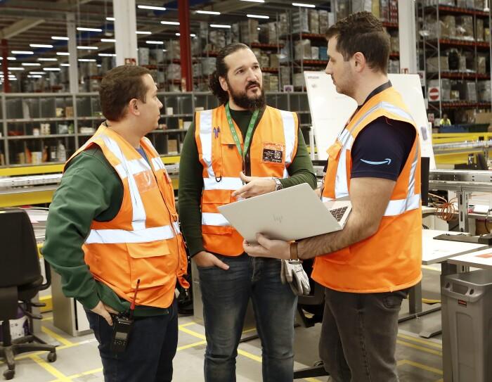 Sergio Amador, lidera el equipo de Health & Safety de los centros de Amazon Operaciones en España. En el centro de la foto con pantalones negros y un chaleco naranja. Rodeado de dos compañeros, el de la derecha lleva un ordenador y un ordenador. De fondo hay meses y estanterías de un centro logístico.