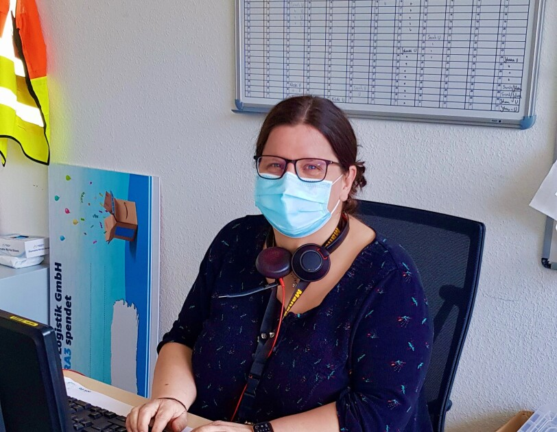 Silvana mit Maske am Schreibtisch.