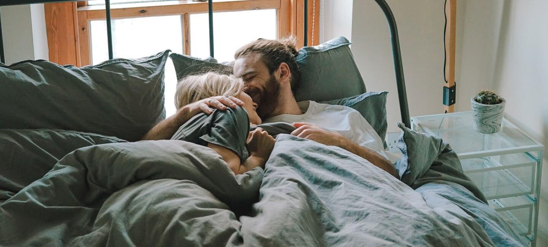Ein junges Pärchen kuschelt im Bett