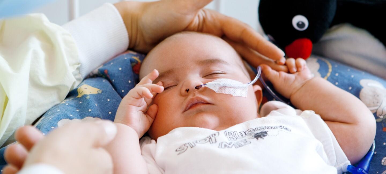 Eine Mutter legt schützend ihre Hand über den Kopf ihres kranken Babys