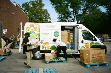 Whole Foods employees unload a vehicle for Nourishing Our Neighborhoods.