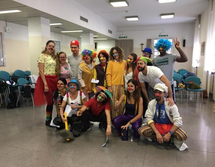 Dipendenti Amazon in gruppo durante il corso di clown terapia. Sono travestiti da clown e indossano nasi di gomma rossi.