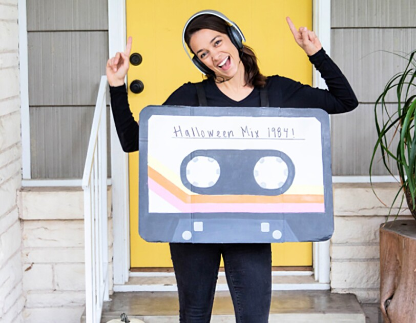 "A woman wears jeans and a long-sleeve tee. over her torso is a box painted to look like a cassette tape, with ""Halloween Mix 1984"" on the front"