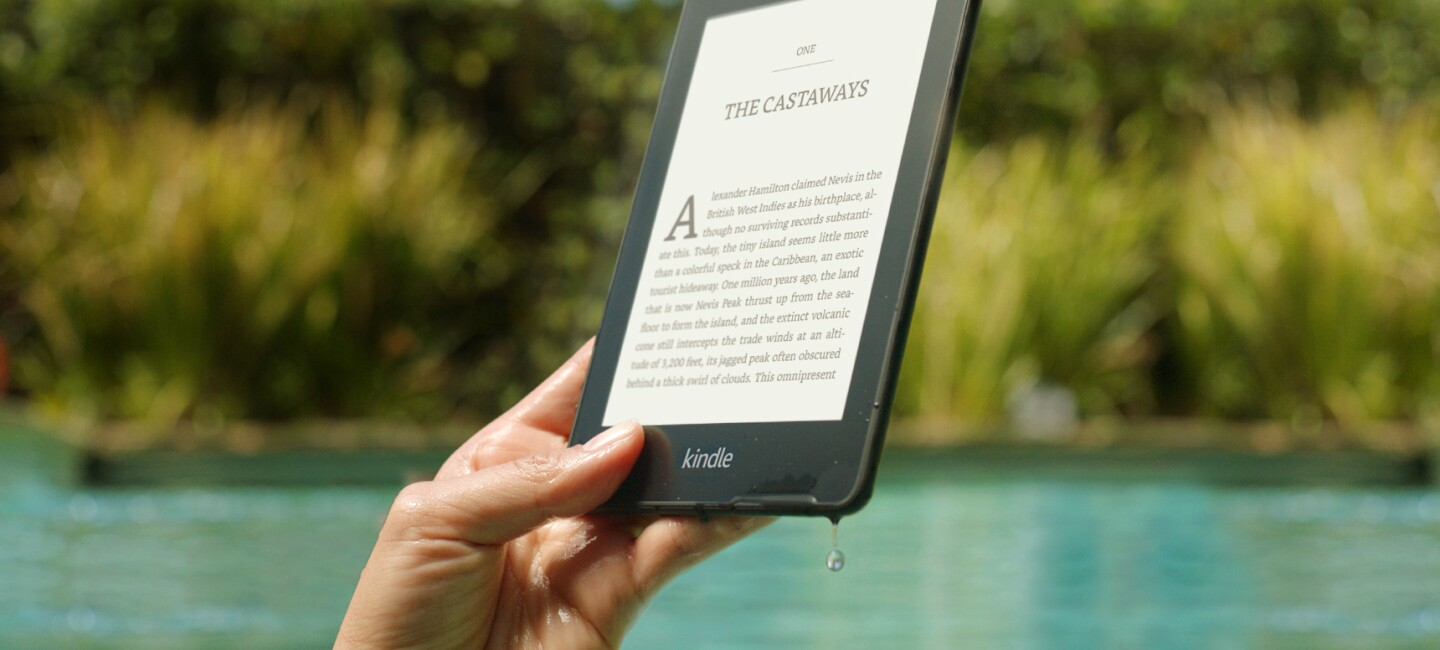 Someone holding their Amazon Kindle Paperwhite by a swimming pool. There is water dripping from the corner of the device.