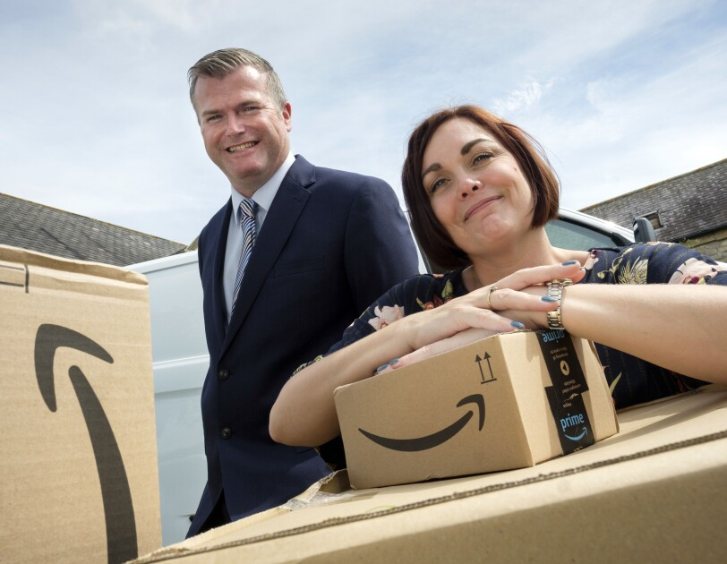 James and Rebecca, owners of JMHC Logistics, standing behind Amazon boxes.