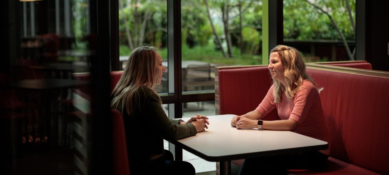 Zwei Mitarbeiterinnen sitzen sich am Tisch gegenüber und unterhalten sich.