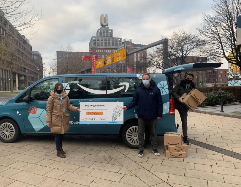 Amazon Van mit Mitarbeitern und Spendenscheck.