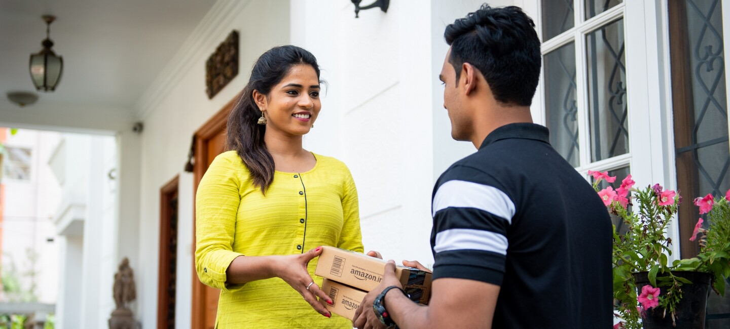 A lady receives an Amazon parcel from an associate
