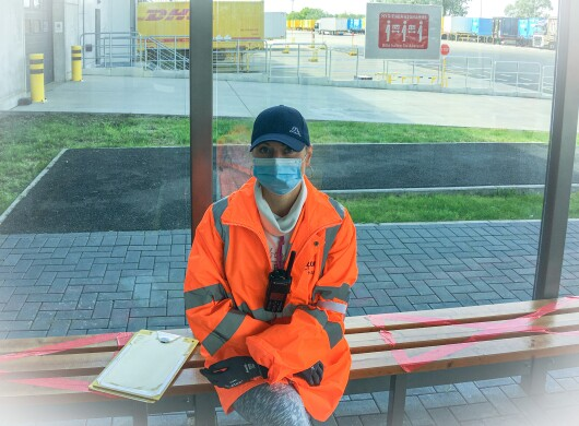 Eine Frau in orangener Sicherheitsjacke und mit Mundschutz