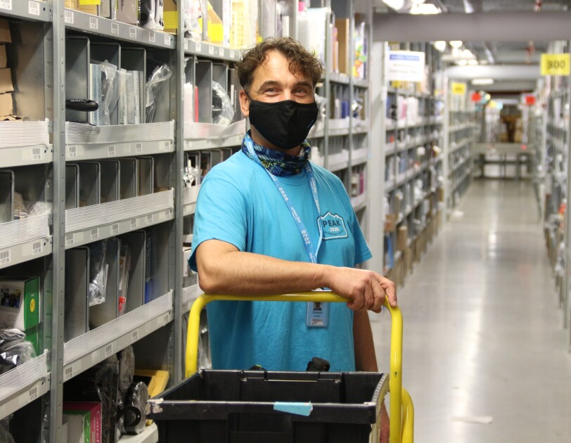Ein Mitarbeiter mit Maske und blauem T-Shirt in einem Regalgang.