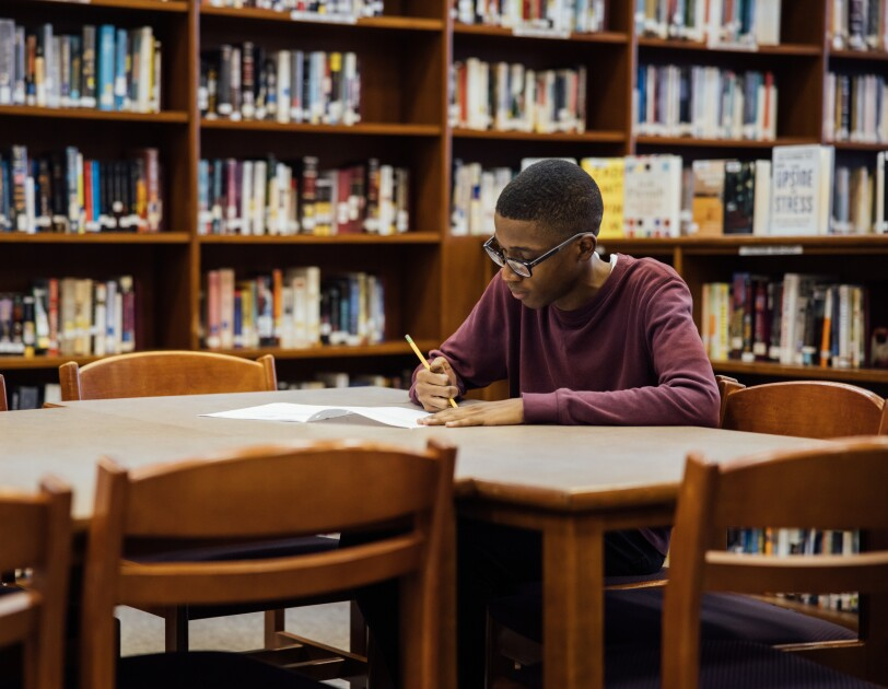 A teenage boy wearing glasses sits at a table in a library. He holds a pencil in his right hand and writes on a paper.
