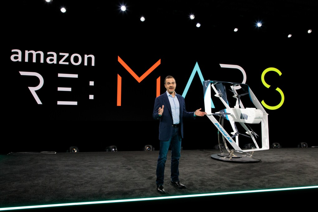 A man stands on a stage where an aerial drone is displayed.
