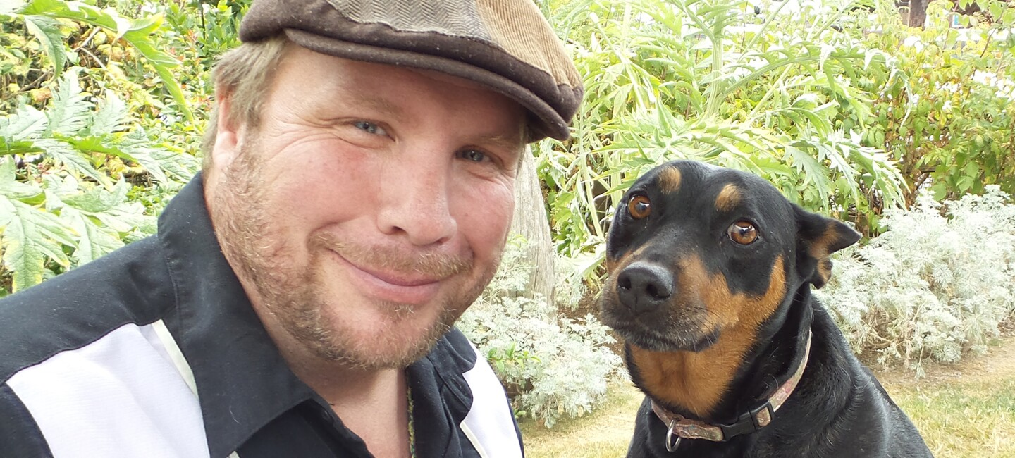 An Amazon author in a cap in the woods with his brown and black dog.