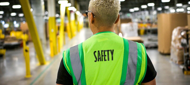 Ein Mitarbeiter mit Sicherheitsweste im Logistikzentrum