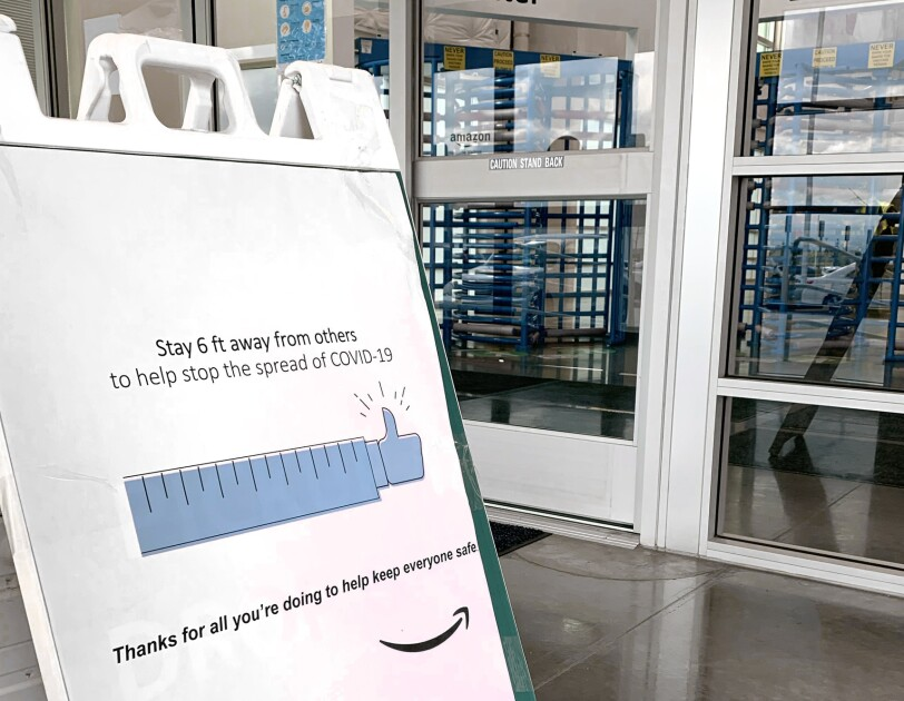 "Signage at the entry for an Amazon fulfillment center that says ""Stay 6 ft away from others to help stop the spread of COVID-19. Thanks for all you're doing to help keep everyone safe."""