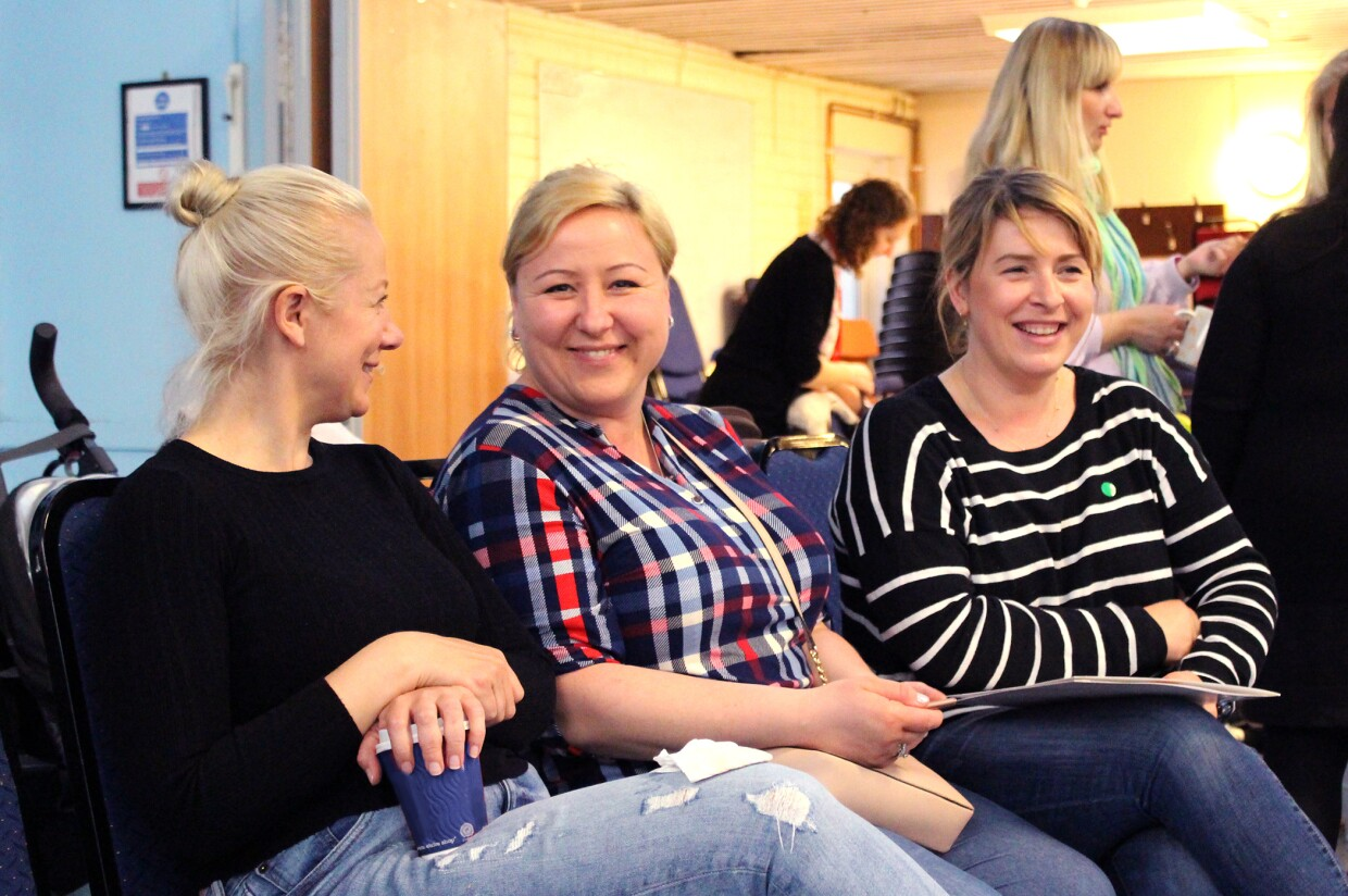 In Kind Direct charity photograph of three people sitting next to each other smiling
