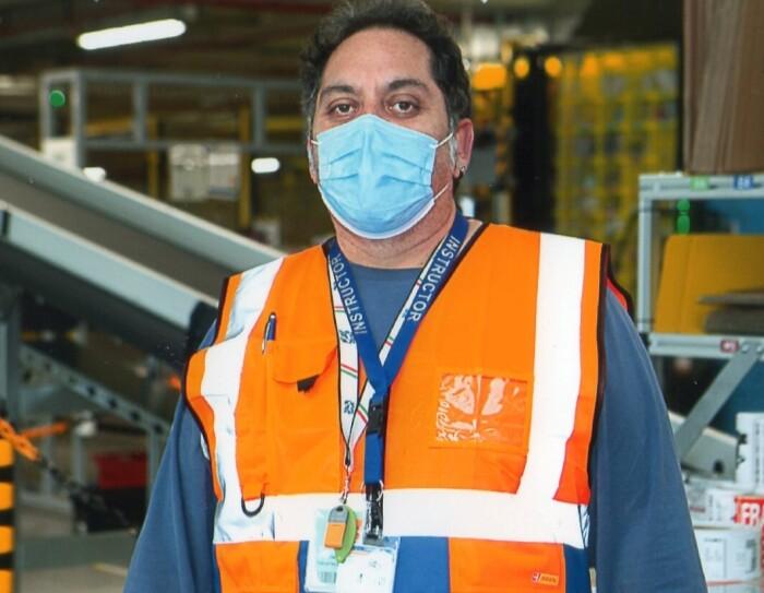 Uomo ripreso a mezzo busto all'interno di un magazzino Amazon. Indossa una mascherina chirurgica sul volto e un giubbino catarinfrangente arancione. Al collo porta appesi due cordini porta-badge.