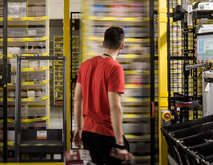 amazon employee in red t-shirt standing infront of moving shelves