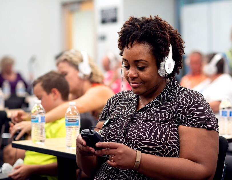 A woman wears white headphones and looks at a small black device. More people in headphones can be seen in the background.