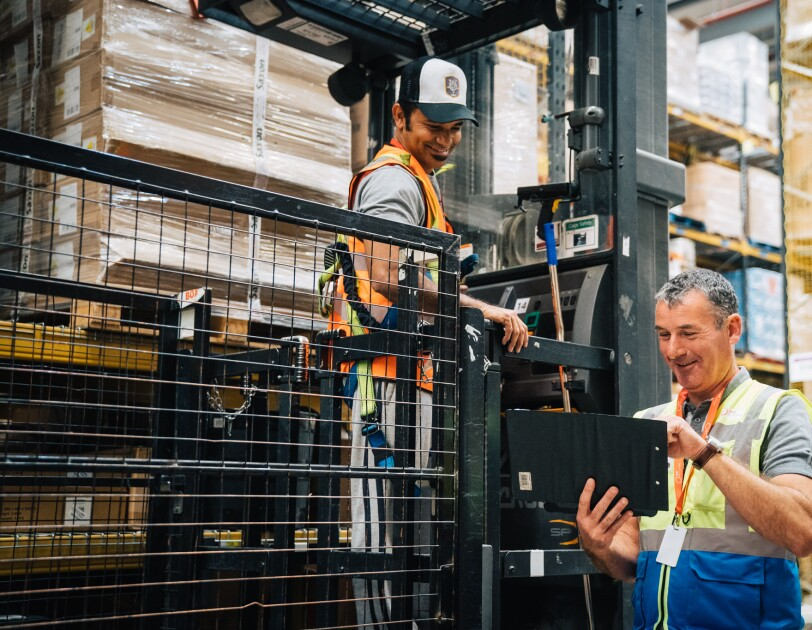 Temporary associate John Sheerin smiling at a colleague in an Amazon Fulfilment Centre and typing on a tablet.