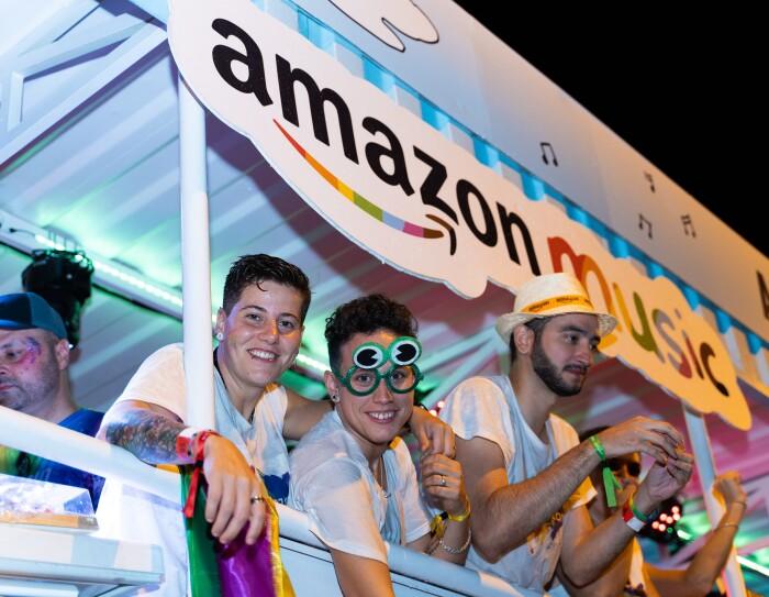 Susana Torres y María García posan desde la carroza de glamazon durante el desfile del Día internacional del orgullo LGTBI en Madrid. Susana abraza por el cuello a María que le tiene la mano sujeta. Las dos miran sonriendo a cámara. María lleva unas gafas de juguete de color verde.