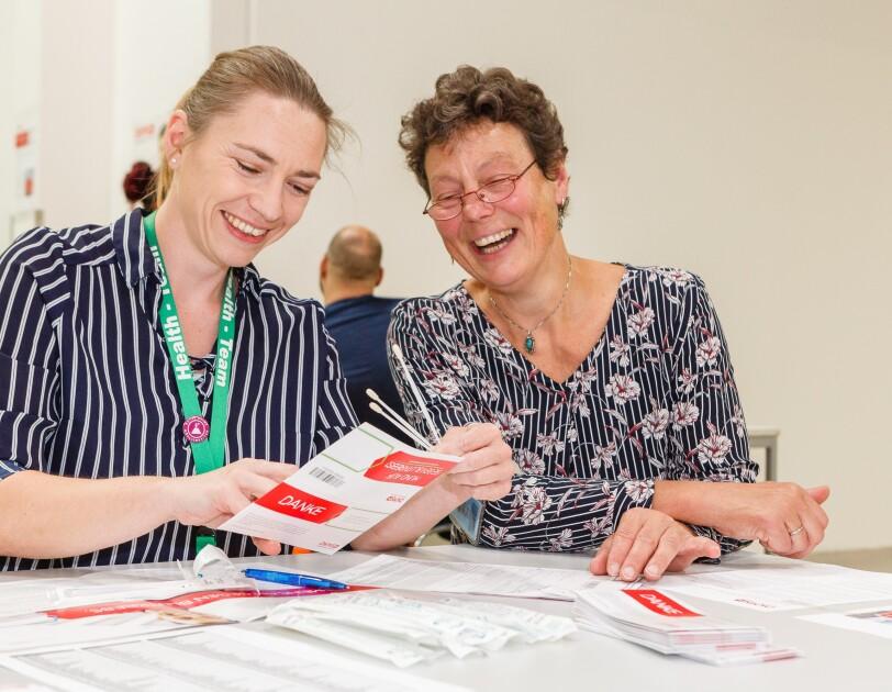 Zwei lächelnde Mitarbeiterinnen sitzen an einem Tisch, vor ihnen DKMS-Registrierkarten und Wattestäbchen
