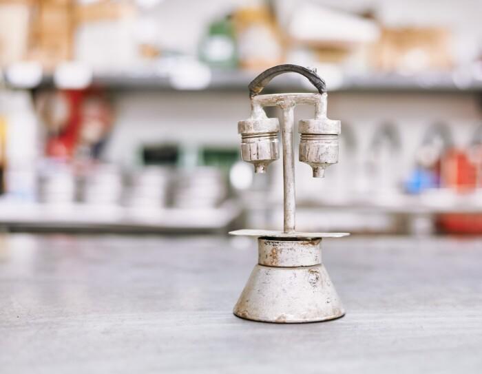 Foto di un prototipo di Kamira, piuttosto ossidato, composto da pezzi di varie caffettiere rimontati da Nino Santoro. Questo ha due bocchette per far uscire il caffé e un manico ad arco nella parte superiore.