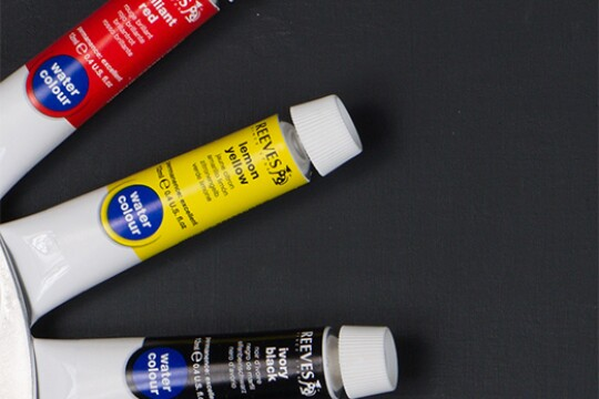 "Three tubes of paint are arranged in a radial pattern. The top tube is labeled ""brilliant red."" The middle is ""lemon yellow."" The bottom is ""ivory black."""