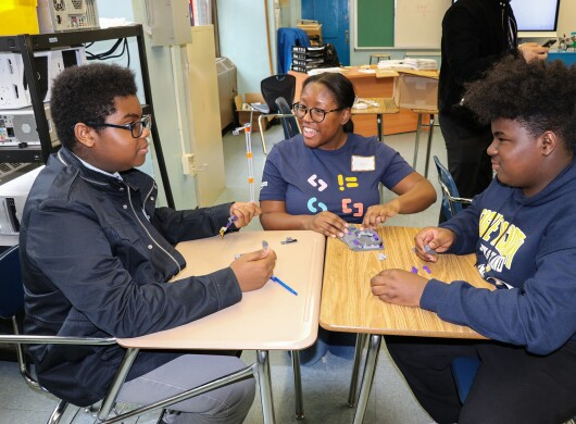 Three students work on hands-on STEM learning activities.