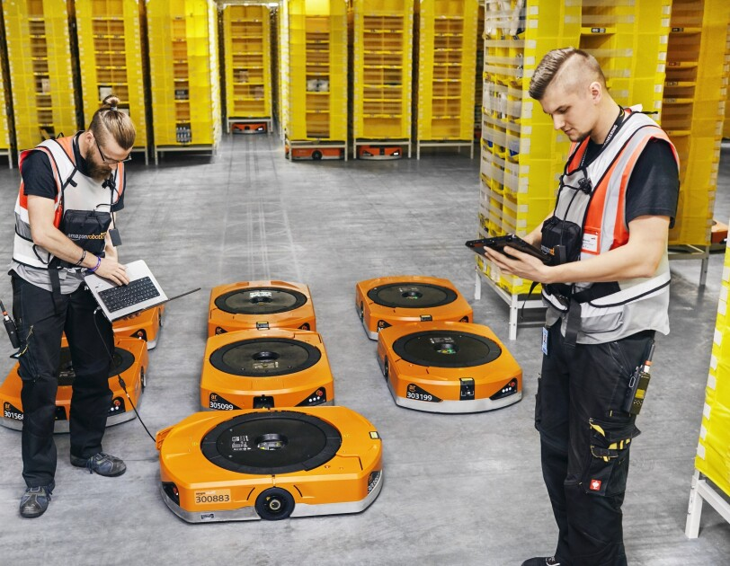 Dwóch pracowników Amazon z robotami w centrum logistyki