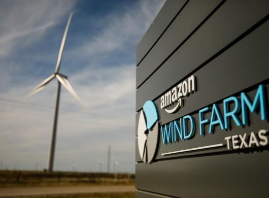 Parco eolico di Amazon in Texas. Pala eolica sullo sfondo con cielo azzurro e nuvole. Logo Amazon Windfarm Texas in primo piano, scritto in bianco e celeste.