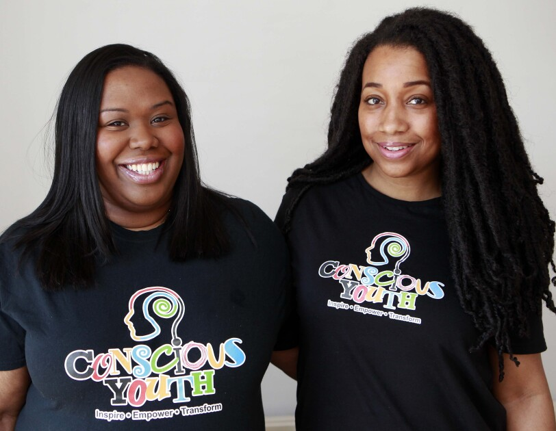 An image of Sophie and Serena from Conscious Youth, they are wearing t shirts with their logo on it.