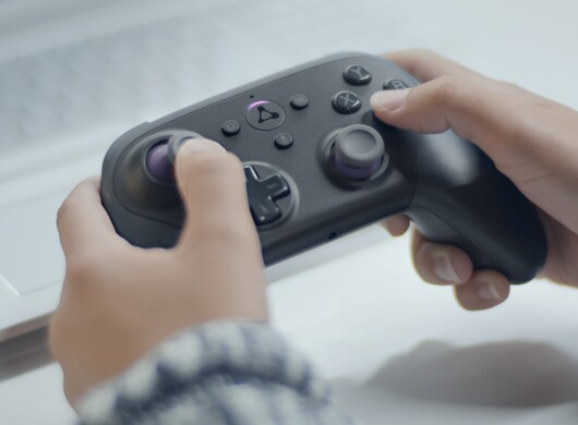 A person holds a gaming controller while playing a video game.