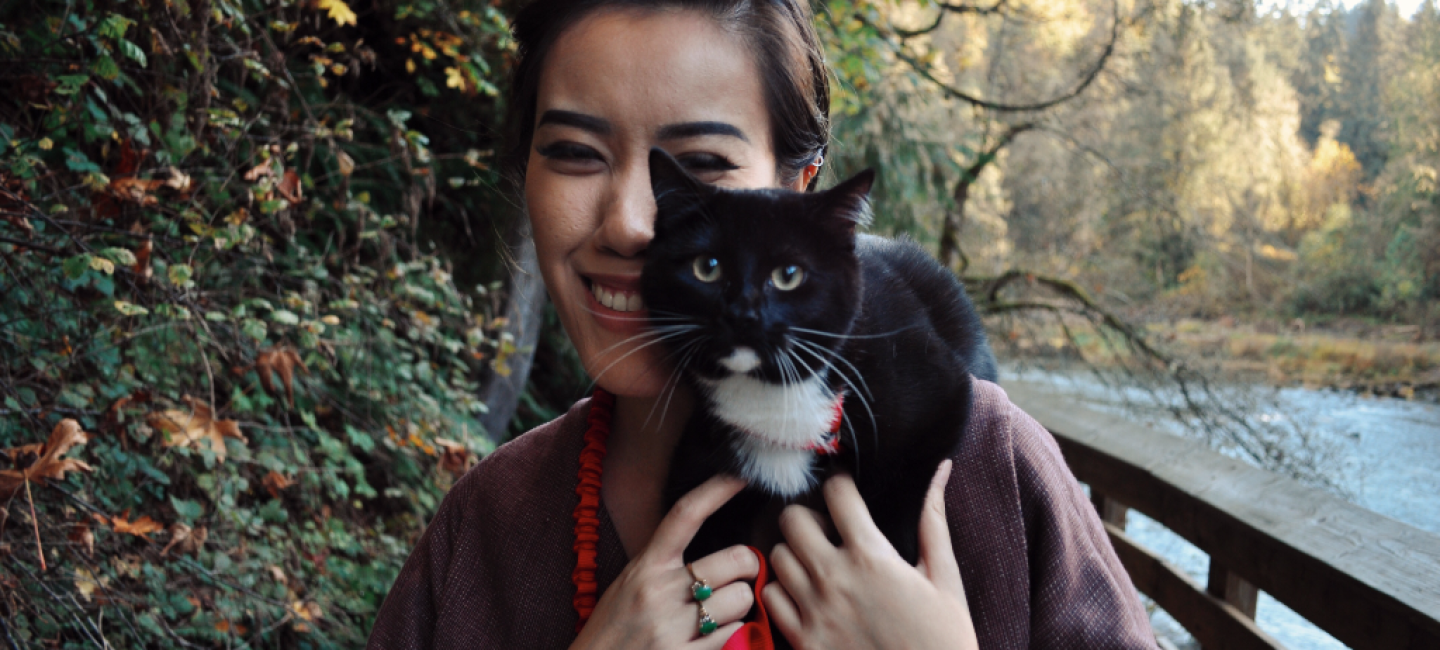 A woman wearing a purple coat, who is an Amazon intern, holding a black cat standing on a bridge next to a river.