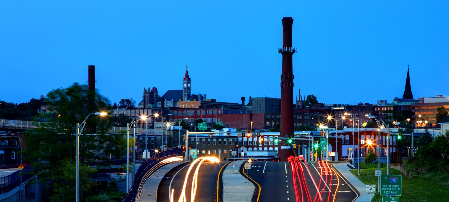 Downtown Fall River, Massachusetts in the evening, showing the town's smokestack, church steeples, and streaks of traffic on the highway, with the city skyline in the back.